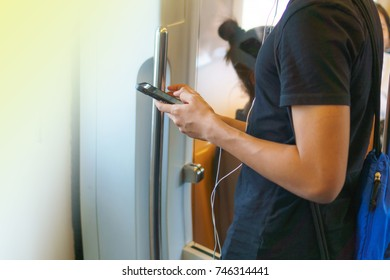 Cropped view of Young man using the phone on the train