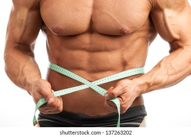 Cropped view of young muscular man with measuring tape around his waist