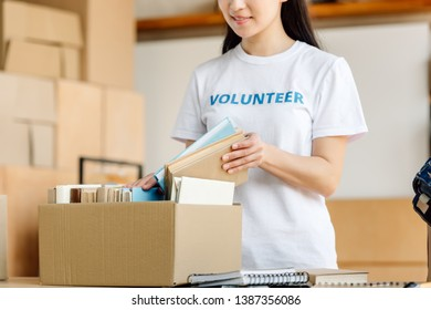 cropped view of young volunteer girl unpacking carton box with books