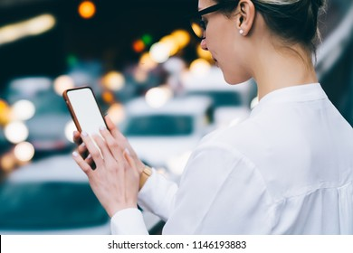 Cropped view of young woman chatting online in social networks with followers on smartphone with blank display on bokeh background.Female blogger holding phone with mock up area for internet website