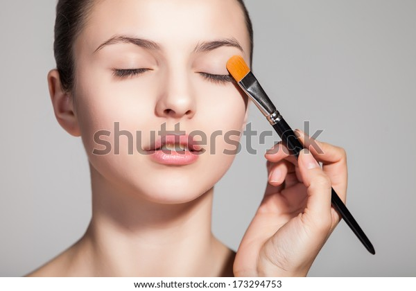Cropped view of a young woman having eyeshadow added to her eyelids