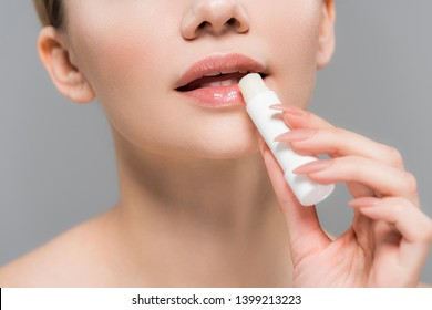 cropped view of young woman holding lip balm near lips isolated on grey