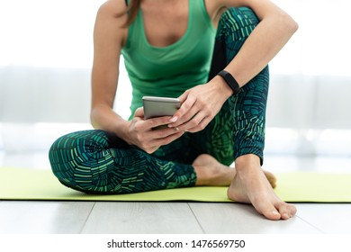 Cropped view of young woman sitting on fitness mat and using smartphone with mobile app after training at home