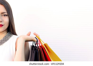 cropped woman face, half face, teenager holding or carry shopping bags, big space for text on white background