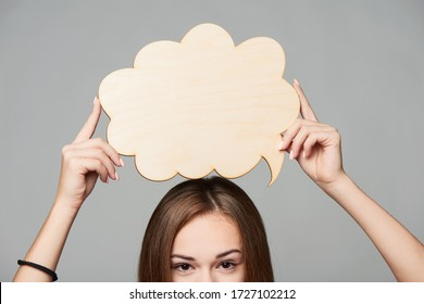 Cropped woman face holding thinking bubble above, over grey background