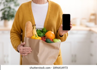 Cropped of woman with shopping bag full of grocery showing smartphone with empty screen, kitchen interior, copy space, mockup. Unrecognizable lady using mobile app for grocery shopping online