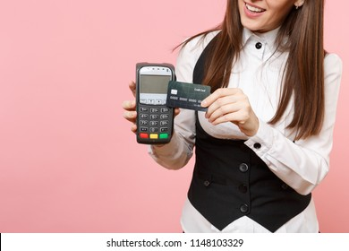 Cropped Young business woman holding wireless modern bank payment terminal to process and acquire credit card payments, black card isolated on pink background. Lady boss. Achievement career wealth