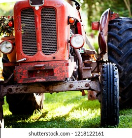 Croppped photo of old vintage red tractor standing on a farm field at sunset.