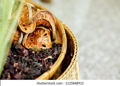 """Crops of dry Thai herbs """"Bael fruit"""" and """"Roselle""""on bamboo basket and blurry background. """"Bael fruit"""" and """"Roselle"""" are popular natural Thai herbs to make for healthy herbal drink water."""