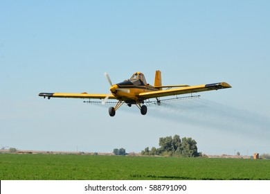 Crops duster airplane spraying pesticides on an alfalfa field in Imperial Valley, California.