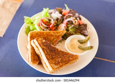 Croque Monsieur sandwich with salad and caramelized onions at a cafe