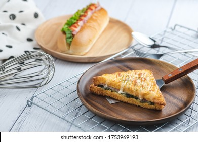 croque monsieur with slices of boiled ham, placed on a wooden plate with cooking tools.