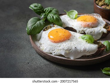 Croque-madame with fried egg , pesto sauce and basil. Traditional French Toasted Sandwich. French cuisine. Copy space, selective focus