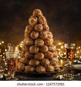 croquembouche, festive profiteroles cake with caramel for Christmas, selective focus, dark background