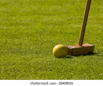 A croquet mallet about to hit a yellow ball on green grass