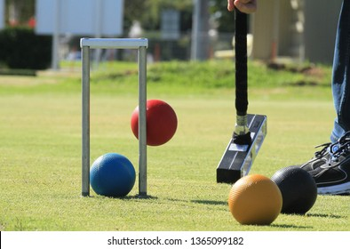 A croquet mallet attempts to hit a red ball over the blue ball and through the hoop.