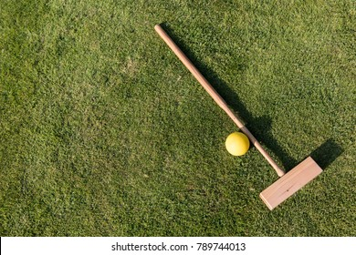 Croquet mallet and ball on a green lawn in summer
