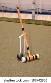 A croquet mallet and ball resting against a hoop