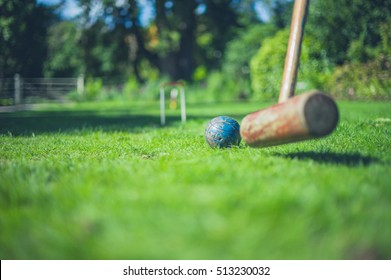A croquet mallet is hitting a ball on a lawn
