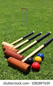 Croquet mallets and balls lying on the lawn.