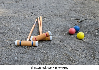 Croquet mallets and balls on the dirt ground