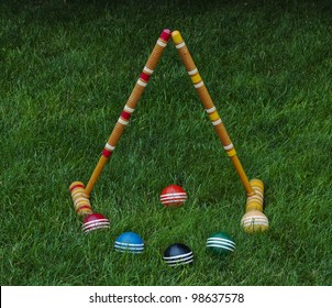 Croquet mallets and balls on grass background