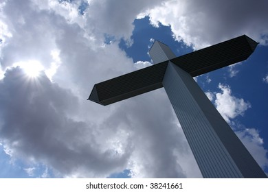 Cross against a cloudy sky with the sun breaking through