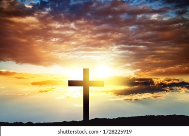 Cross against the sky . Dramatic nature background . Light from sky . Religion background .