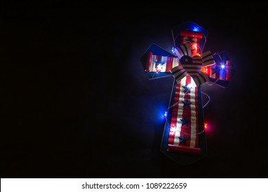 Cross with American Flag surrounded by lights on a black background