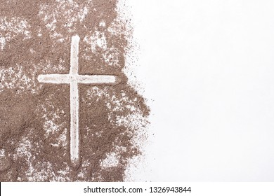 Cross and ash on white background - symbol of Ash Wednesday. Copy space