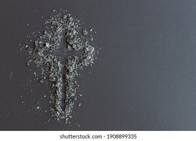 cross of ashes on dark background with copy space