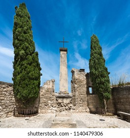 Cross between two cypress trees in Baux-de-Provence. Bouches du Rhone, Provence, France, Europe.
