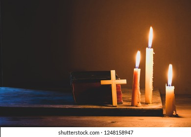 Cross with bible and candle on a old oak wooden table. Beautiful gold background. Religion concept.