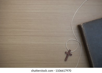 Cross with Bible, wooden christian cross and bible on the old wooden background.