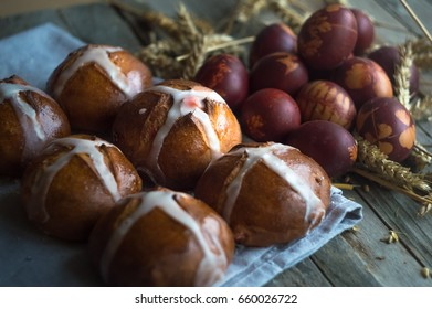 Cross Buns and Traditional Homemade Painted Easter Eggs on Wooden Table