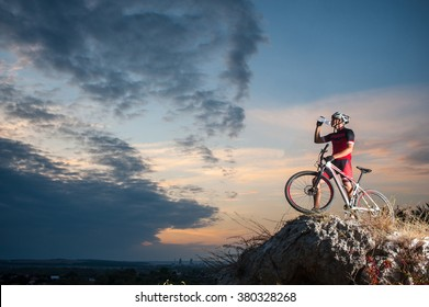 Cross country biker drinking water on top of a mountain with bike in the evening, sky background. side view