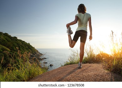 Cross country racer stretching on top of a hill and enjoying sunset sea view