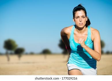 Cross country running sweaty woman. Female runner on countryside training.