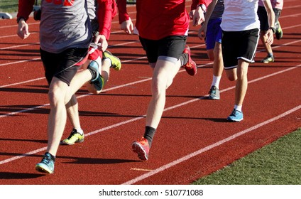 Cross country team training together on a red track wearing spikes