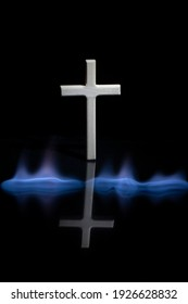 Cross or crucifix with reflection in the darkness. Burning fire flames. Religious theme.