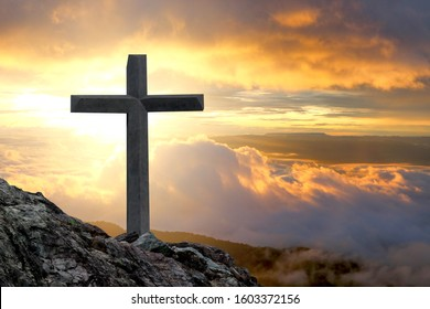 cross crucifixion on a mountain cliff rock With a sunset background