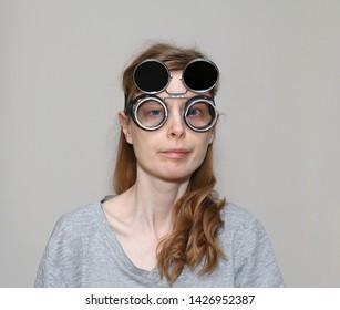 Cross eyed girl with dark welding glasses on her head