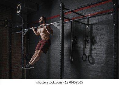 Cross fit athlete doing pull-ups at the gym. Practicing calisthenics. Handsome man doing functional training.