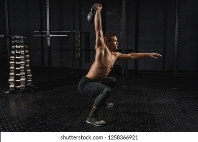 Cross fit training in a gym. Kettlebells swing exercise man workout at gym.