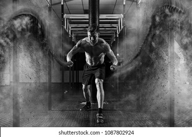 Cross fit training. Man working out with battle ropes at gym