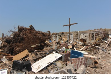 A cross held together by a tattered United States flag is raised above a home totally destroyed by a devastating tornado as proof of the homeowners determination to overcome natures wrath.
