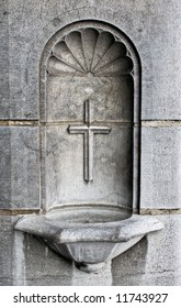A cross and holy water well as part of the architecture in a cathedral