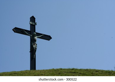 Cross with Jesus at hilltop against bright blue sky