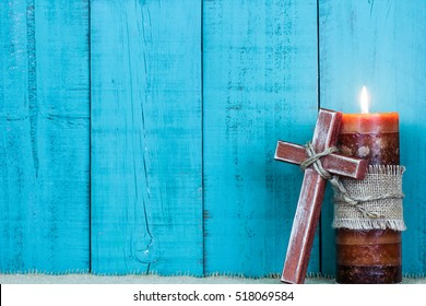 Cross of Jesus resting against burning candle with rope by antique rustic teal blue wooden background; Christmas and Easter holiday background with wood copy space