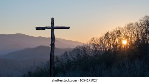 The Cross of Jesus and Sunset through the Trees